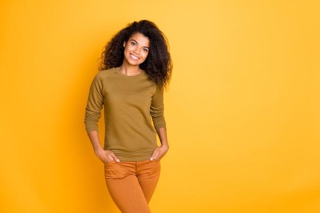 Photo de bonne humeur à la mode positive jolie jolie petite amie charmante tenant la main dans les poches portant un pantalon orange isolé sur fond de couleurs vives près de l'espace vide