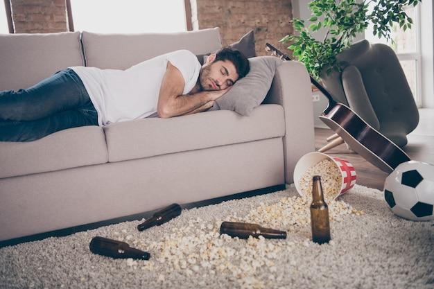 Photo de boozer multiethnique mec alcoolique couché canapé dormir la gueule de bois bière bouteilles vides plancher de pop-corn souffrance après l'enterrement de vie de garçon matin salissant des ordures sale plat à l'intérieur