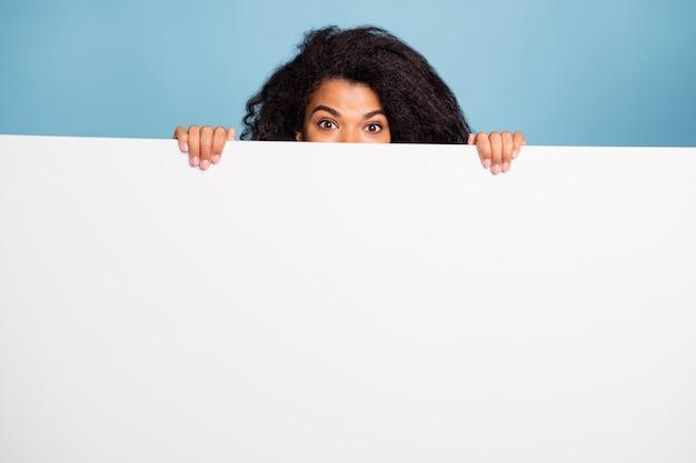 Photo de bouclés ondulés mignon gai aux cheveux bruns positifs vous présentant des informations sur la bannière blanche se cachant derrière la tenue de fond de couleur bleu pastel isolé