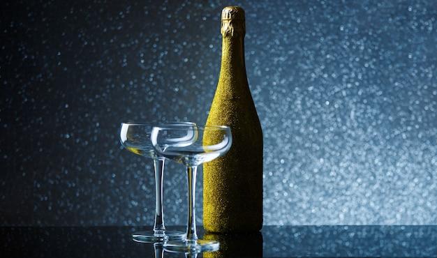 Photo de bouteille de champagne dans un emballage d'or avec un verre de vin vide sur fond gris
