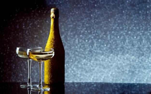 Photo de bouteille de vin dans un emballage d'or avec deux verres à vin sur fond gris