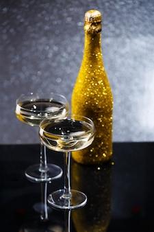 Photo d'une bouteille de vin et de deux verres à vin sur un tableau noir, fond gris avec des taches