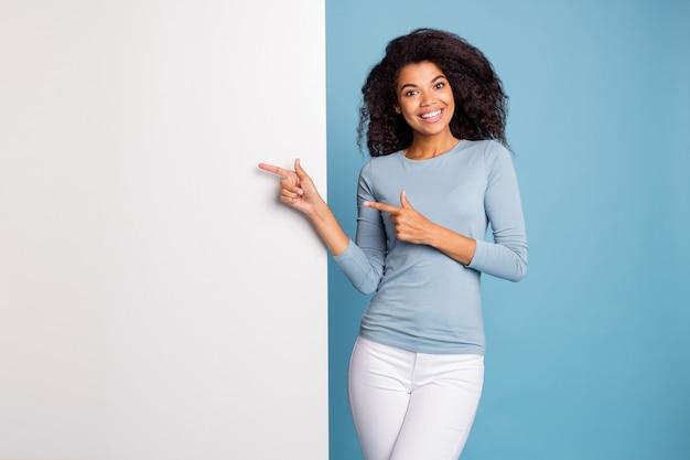 Photo de brune aux cheveux joyeux positif jolie jolie fille ondulée bouclée pointant sur l'espace de la bannière blanche vide dans le pantalon pantalon pull bleu souriant à pleines dents fond de couleur pastel isolé