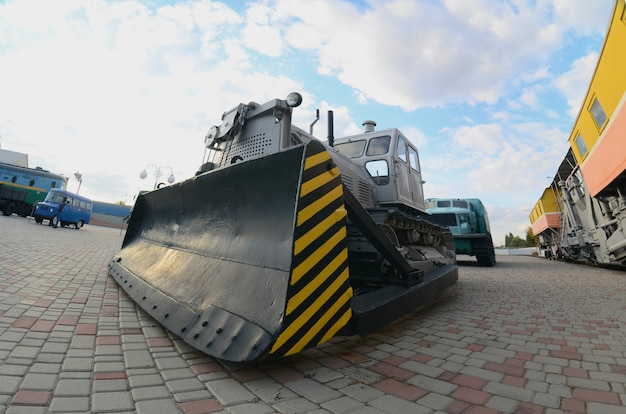 Photo d'un bulldozer gris parmi les trains. forte distorsion de l'objectif fisheye