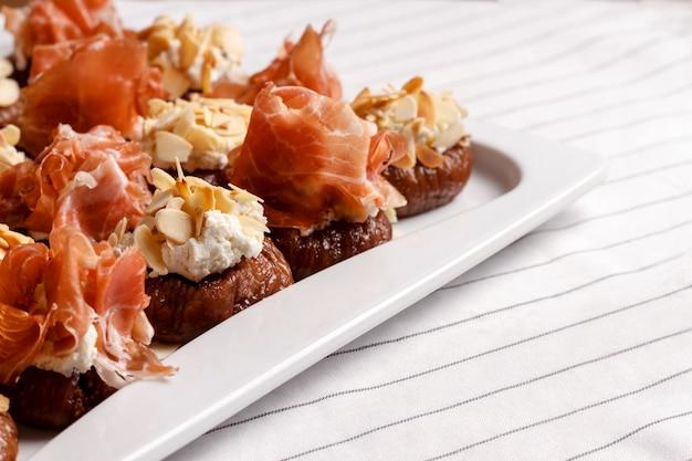 Photo de canapés au fromage et bacon sur mur blanc.