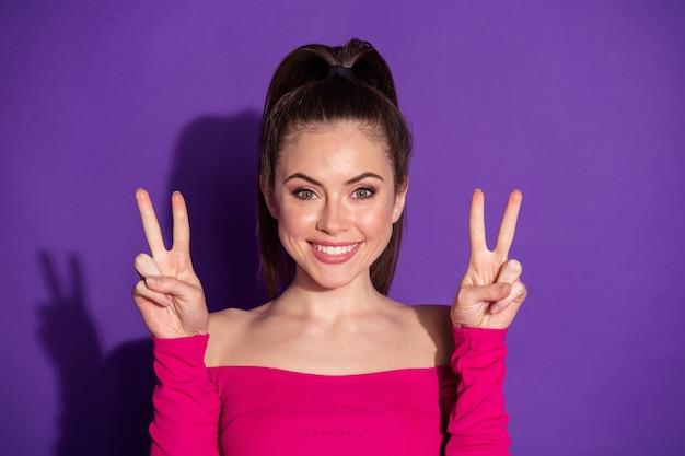 Photo de candide douce fille faire v-sign sourire à pleines dents isolé sur fond de couleur violette