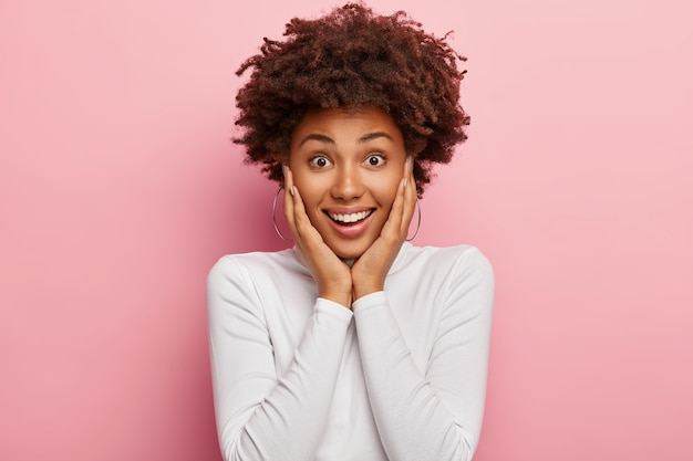 Une photo candide d'une fille heureuse à la peau foncée a une expression faciale heureuse, sourit positivement, touche les joues, porte un pull à col roulé décontracté, des modèles à l'intérieur, ravie d'obtenir une proposition ou une suggestion impressionnante