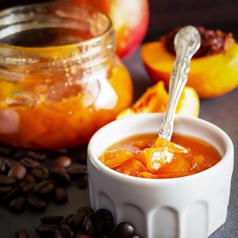 Photo carrée. marmelade de nectarine en ramequin blanc et pot aux grains de café. espace sombre. mise au point sélective. fermer.