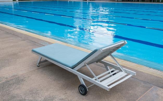 Photo d'une chaise longue au bord d'une piscine d'hôtel ou de villégiature.