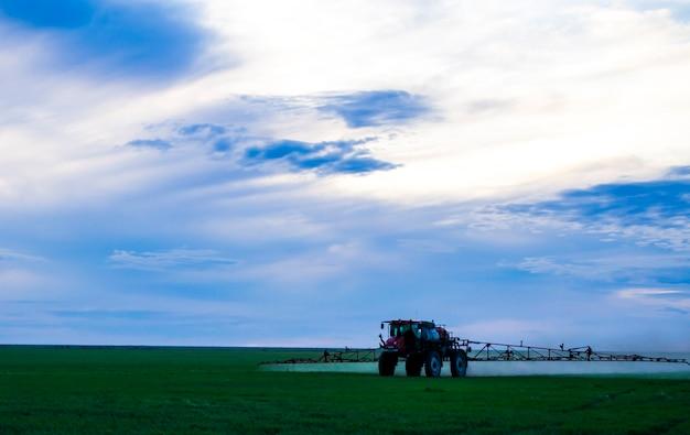 Photo d'un champ de blé pulvérisation d'un tracteur avec des préparations agrochimiques ou agrochimiques sur un youn