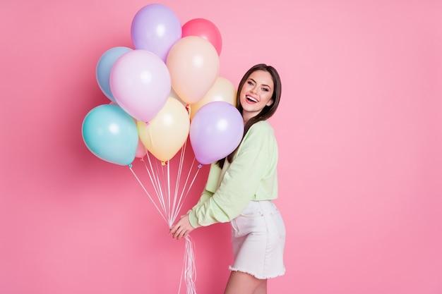 Photo de charmante dame fête d'anniversaire meilleur ami invité tenir de nombreux ballons à air félicitations porter décontracté vert pull pull jeans mini jupe isolé rose fond de couleur pastel