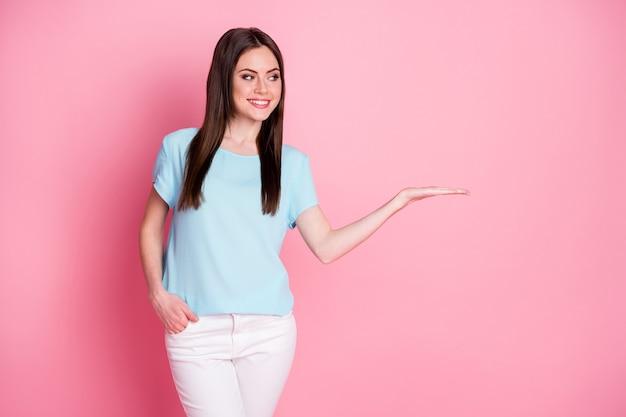 Photo d'une charmante dame tenir bras ouvert espace vide porter un t-shirt décontracté pantalon blanc isolé fond de couleur pastel rose