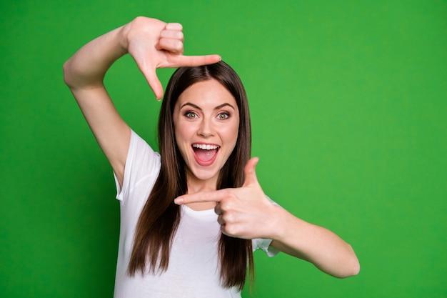 Photo d'une charmante fille énergique portant un t-shirt blanc faisant des doigts photo bouche ouverte fond de couleur vert isolé
