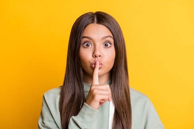 Photo d'une charmante fille enfant vêtue d'une tenue verte décontractée, la bouche du doigt ne demande pas de dire des secrets isolés sur fond de couleur jaune