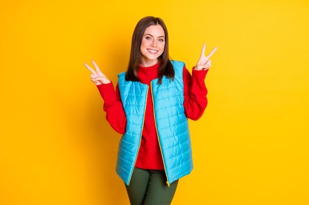 La photo d'une charmante fille séduisante a profité des vacances d'automne pour faire de la saison des vêtements de signe v bon look pantalons de vêtements isolés sur fond de couleur brillant