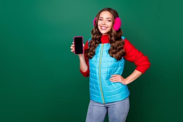 Photo de charmante jeune femme mignonne spectacle téléphone espace vide main hanche souriante présentant un nouveau modèle porter des cache-oreilles roses gilet zippé bleu pull rouge isolé fond de couleur verte