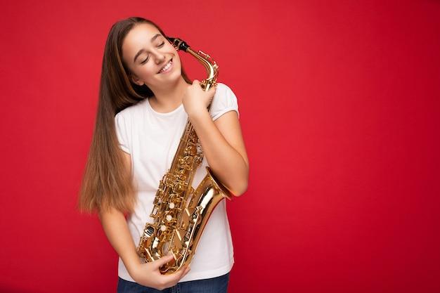Photo d'une charmante petite adolescente brune souriante et souriante portant un t-shirt blanc pour la maquette