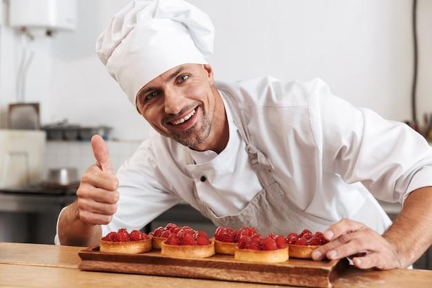 Photo de chef masculin professionnel en uniforme blanc tenant la plaque avec des gâteaux