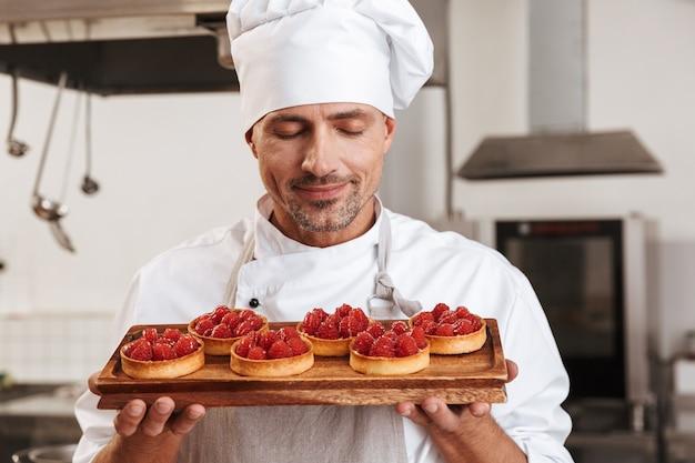 Photo de chef masculin de race blanche en uniforme blanc tenant la plaque avec des gâteaux