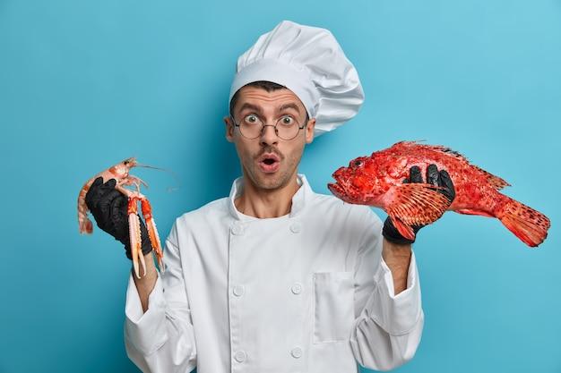 Photo d'un chef qualifié choqué tient des écrevisses, des bars rouges, prépare un délicieux plat de fruits de mer, travaille sur son menu de poissons, garde la bouche ouverte avec émerveillement