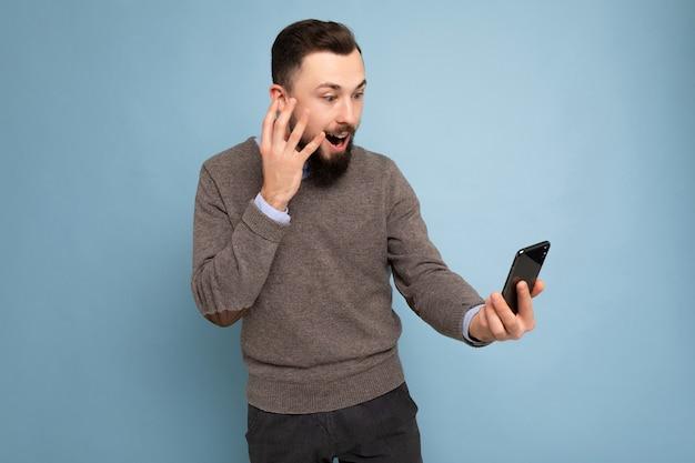 Photo de choqué positif beau jeune homme non rasé brune avec barbe portant un pull gris décontracté et une chemise bleue isolée sur un mur de fond rose tenant un smartphone ayant un appel vidéo regardant mo