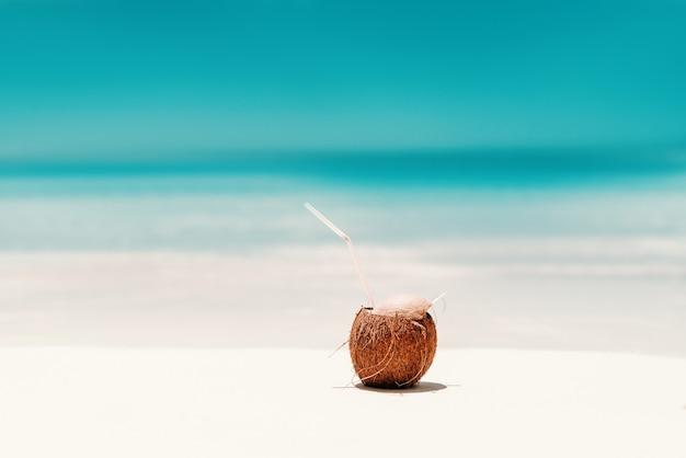 Photo de cocktail à la noix de coco sur la plage.