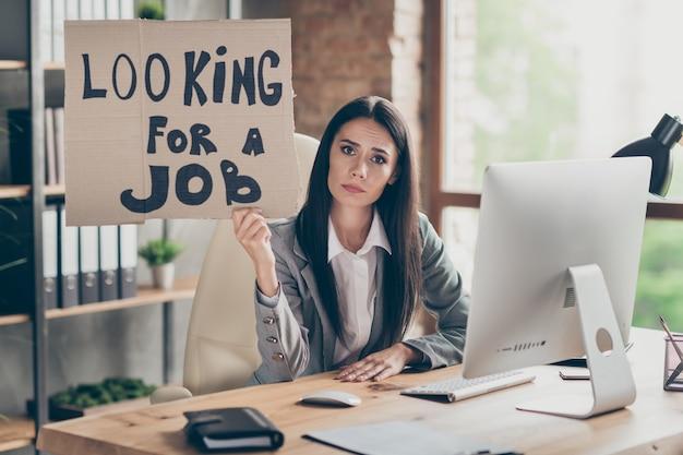 Photo d'une commerçante frustrée, triste et bouleversée, assise sur une table de bureau, emploi perdu, crise du marché de la quarantaine, tenir du texte en carton, chercher un emploi, porter un blazer gris dans le bureau du poste de travail