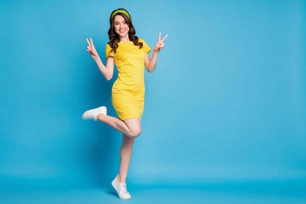 Photo complète du corps d'une charmante dame charmante se sentant énergique faire un signe v isolé sur un fond de couleur bleue