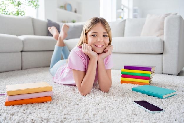 Photo complète du corps d'une charmante jolie fillette allongée sur un tapis de sol profitez d'une étude à distance de la quarantaine du virus corona dans la maison à l'intérieur