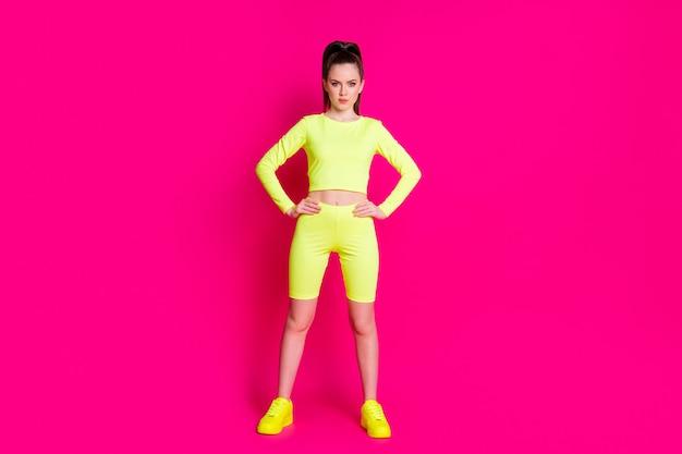 Photo complète du corps d'un entraîneur d'aérobic sportif sérieux mettre les mains à la taille isolée sur fond de couleur rose vif