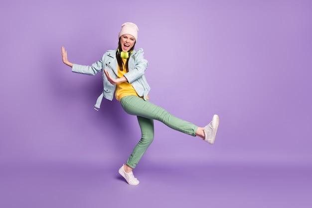 Photo complète du corps d'une femme séduisante et funky street vêtements élégants bonne humeur danse jeune bouge lever les mains jambe haute usure chapeau décontracté veste pantalon chaussures isolé fond de couleur violet