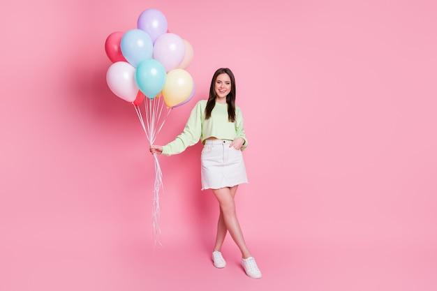 Photo complète du corps d'une femme séduisante organiser une fête d'anniversaire surprise, le meilleur ami tenir de nombreux ballons à air porter des pulls verts décontractés en jean jupe chaussures isolées fond de couleur pastel rose