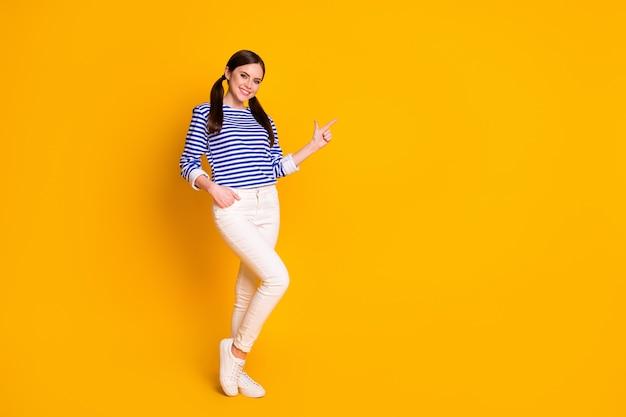 Photo complète du corps d'une fille positive, pointer le fond du doigt, démontrer la promotion de la publicité, profiter des remises sur les ventes de commentaires, porter des vêtements blancs de belle apparence, isolés sur un fond de couleur vive