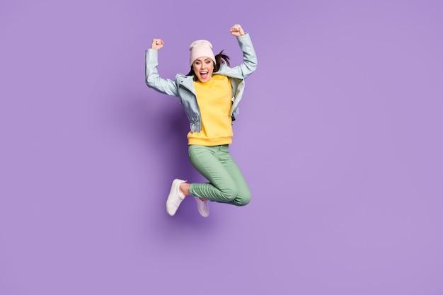 Photo complète du corps d'une jolie dame funky vêtements élégants sauter haut champion de réjouissance criant de bonne humeur porter un chapeau décontracté veste pantalon vert chaussures isolé fond de couleur violet