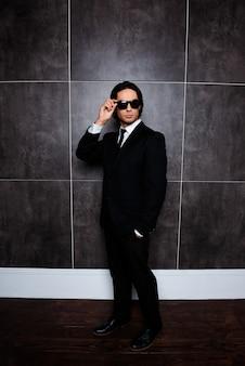 Photo complète d'un homme d'affaires sérieux prospère en costume noir et lunettes