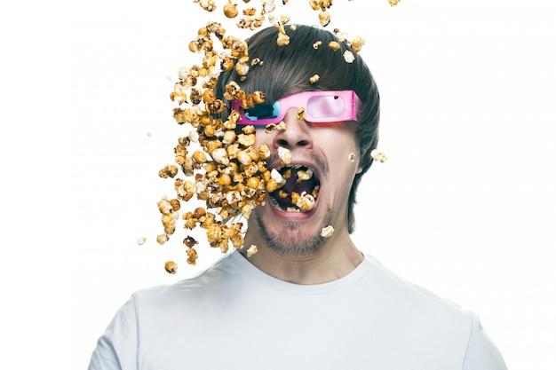 Photo conceptuelle du jeune homme dans des verres stéréo de manger du pop-corn