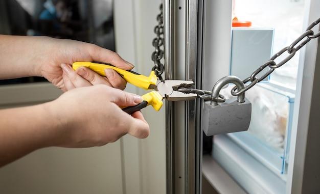 Photo conceptuelle de femme essayant de couper la chaîne sur le réfrigérateur avec des pinces