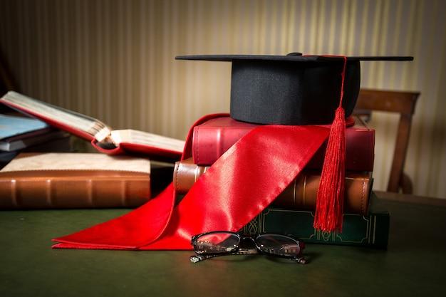 Photo conceptuelle en gros plan du chapeau de graduation et du ruban rouge allongé sur des livres à la bibliothèque