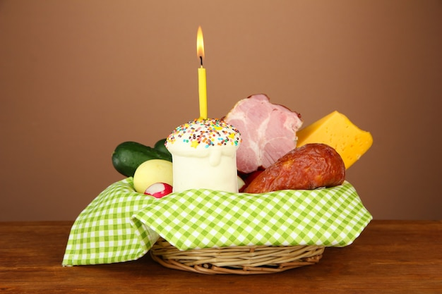 Photo conceptuelle de la nourriture traditionnelle de pâques dans le panier en osier, sur la table en bois sur la couleur