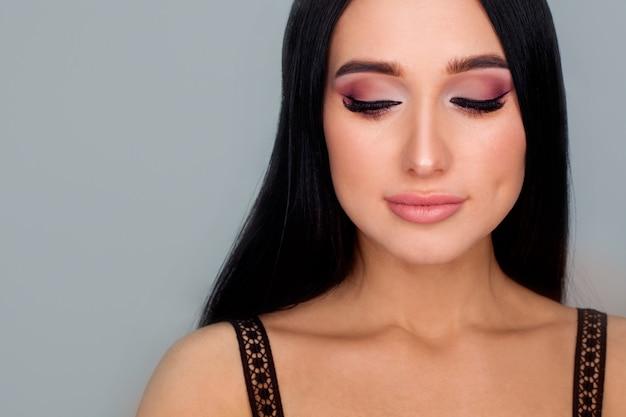 Photo conceptuelle pour la publicité des ombres ou du travail et étude d'une maquilleuse. visage du modèle avec beau maquillage gros plan sur un mur blanc.