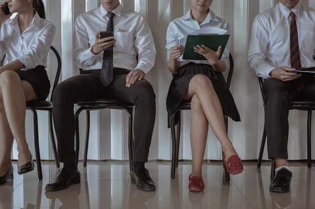 Photo conceptuelle quatre jeunes multiethniques sont assis dans la file d'attente tenant des appareils électroniques utilisant internet en attendant un entretien d'embauche. génération accro aux appareils modernes, emploi, ressources humaines