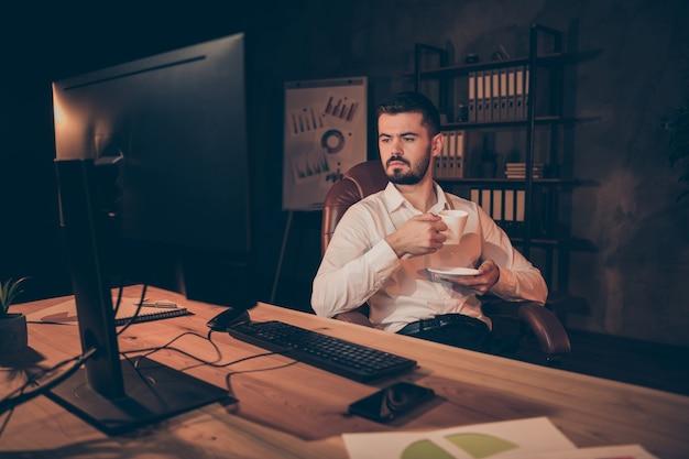 Photo de confiant assistant assis chaise tenir tasse look pc