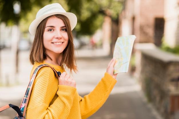 Photo de côté d'une femme souriante qui voyage