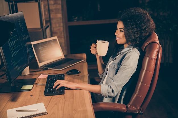Photo côté profil administrateur fille positive s'asseoir table de soirée tenir mug