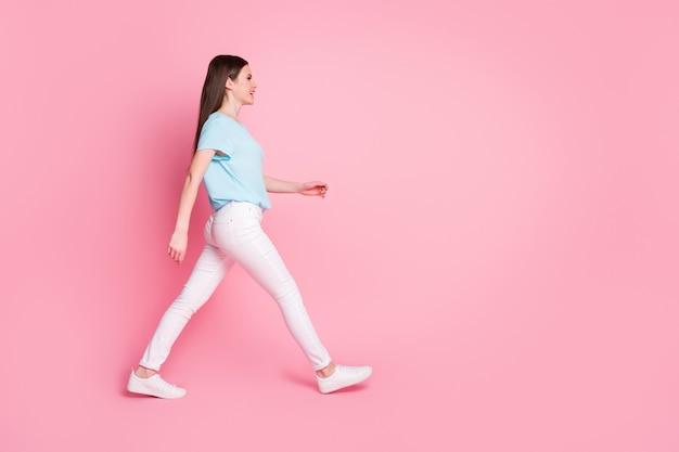 Photo de côté de profil complet du corps de nice girl walk copyspace isolé sur fond de couleur rose