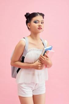 Photo de côté de profil de fille positive tenir des livres de copie aller marcher leçon en classe bibliothèque de conférences isolées sur fond rose