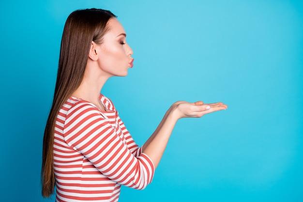 Photo de côté de profil d'une jolie fille charmante amant tenir la main envoyer un baiser d'air copyspace son petit ami porter une bonne chemise isolée sur fond de couleur bleu