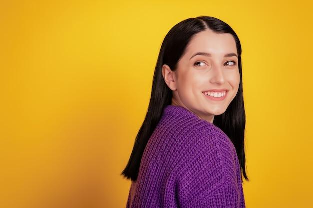 Photo de côté de profil de jolie jeune femme heureuse sourire positif look mignon espace vide sur fond jaune
