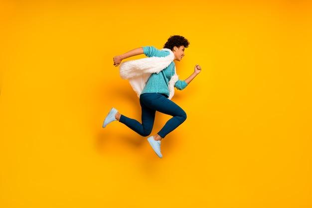Photo de côté de profil pleine taille folle belle fille afro-américaine sauter courir dépêchez-vous des réductions portent un pull bleu sarcelle élégant à la mode pantalon bleu blanc pantalon baskets mur de couleur jaune isolé