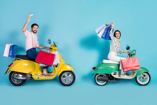 Photo de côté de profil pleine taille ravi deux personnes pilote pilote motocyclette transport boutique centre centre commercial magasin montrer sacs aubaines carte de débit vêtements de cérémonie vêtements isolés mur de couleur bleu